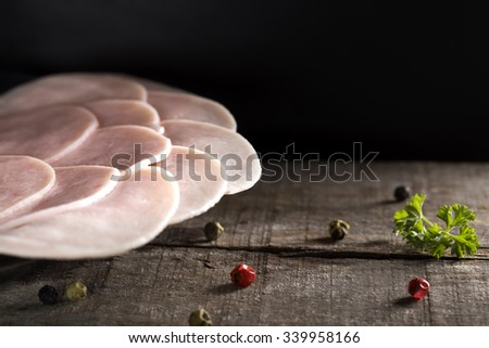 Slices of smoked ham on plate with pepper and parsley over wood - stock photo