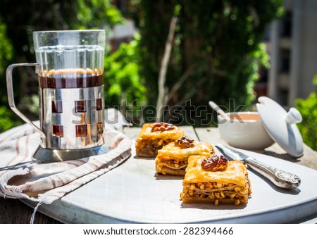slices of sweet baklava on the plate green garden background, traditional Turkish dessert, selective focus - stock photo