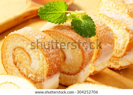 Slices of sweet. creamy roll on a cutting board - stock photo