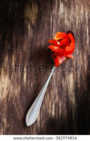 Slices of sweet paprika in old metal spoon. Ingredient for different dishes. View from above. Copy space background - stock photo