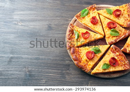 Slices of tasty cheese pizza with basil and cherry tomatoes on table close up - stock photo