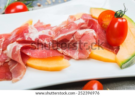 Slices of tasty traditional spanish ham serrano with melon on a white plate with decor herbs and tomatoes - stock photo