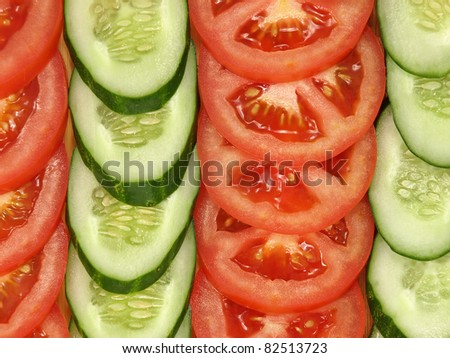Slices of tomatoes and cucumbers arranged in a row suitable as background. - stock photo