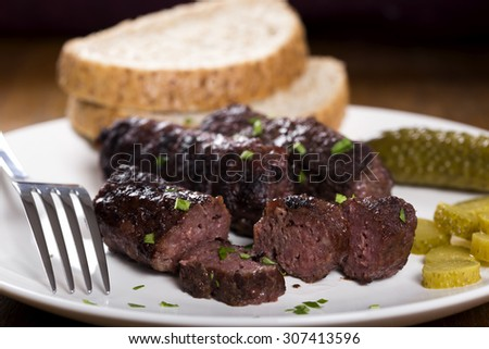 "Slices of traditional food ""mici"" spicy meat balls on plate with pickled cucumbers - stock photo"