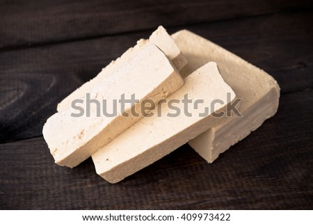 Slices of uncooked tofu on rustic wooden background. Ingredient for vegetarian cuisine - stock photo