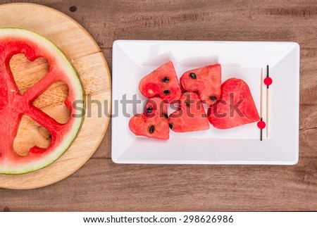 Slices of watermelon in the heart shape on vintage wooden table. Top view - stock photo