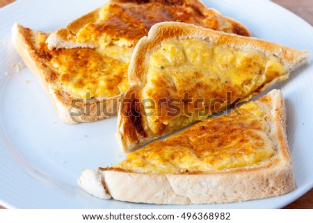 Slices of welsh rarebit, a type of cheese on toast, on a white plate