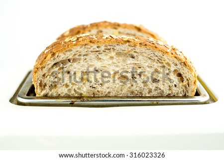 Slices of whole wheat bread in toaster - stock photo