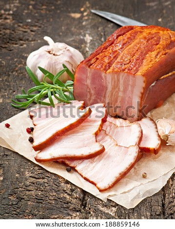 Slices smoked bacon on the old wooden background - stock photo