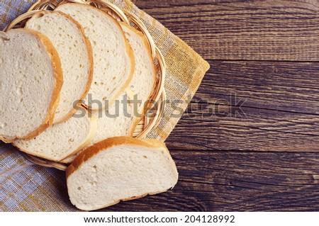 Slices white bread in plate on vintage wooden table with copy space - stock photo