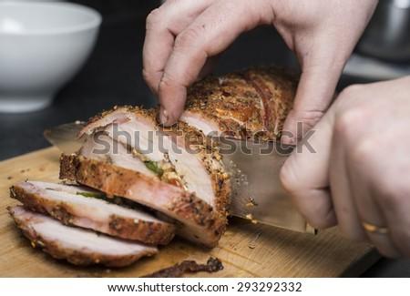 Slicing filled pork fillet on wooden board - stock photo