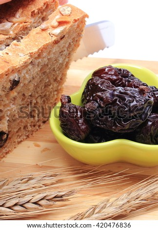 Slicing fresh baked wholemeal bread, heap of dried plums and ears of wheat lying on cutting board, concept for healthy eating - stock photo