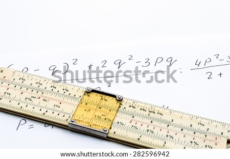 Slide rule lying on a sheet of paper with written formula - stock photo