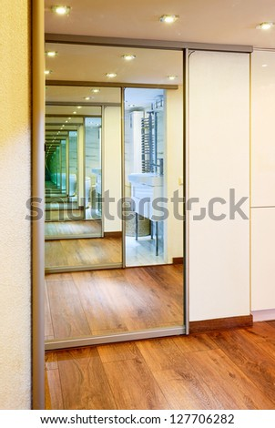 Sliding-door mirror wardrobe in modern hall interior with infinity reflections - stock photo