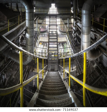Sliding down the stairs with our eyes, floating between the lines to go down to the next floor. A great overlook of a metal constructed staircase inside the belly of this huge power plant. - stock photo