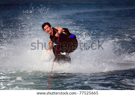 sliding wake-boarder with closed eyes in water splash - stock photo