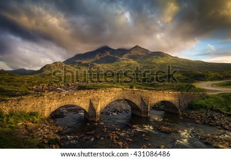 Sligachan Bridge and cloudy Black Cuillins in sunset light, Isle of Skye, Scotland - stock photo