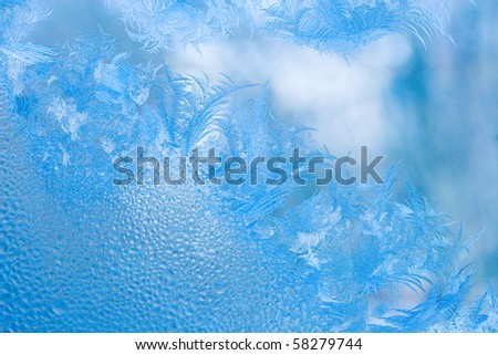 Slightly blurred beautiful frost pattern and drops of water on a window glass (as an abstract winter background) - stock photo