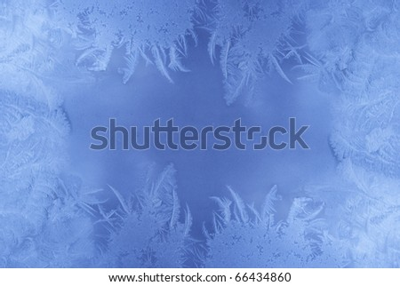 Slightly blurred blue frost pattern on a window glass (with empty space for your text or image) - stock photo