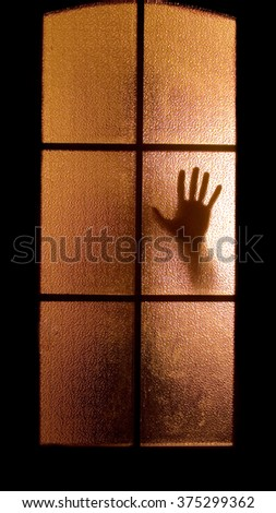 Slightly blurred silhouette of a hand behind a glass door (symbolizing horror or fear) - stock photo