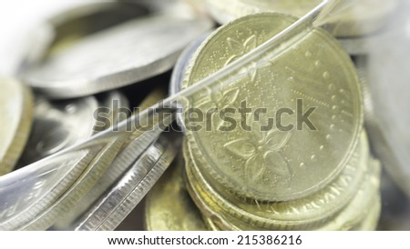 Slightly defocused Malaysia gold coins or small change in transparent hourglass.