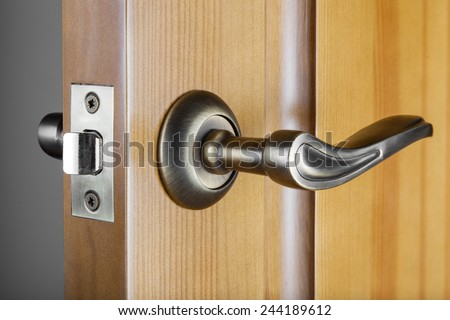 Slightly opened wooden door with latch handle closeup - stock photo