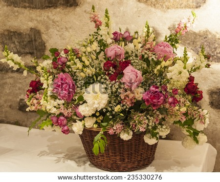 Slightly sepia-toned image (natural colours) of a basket of flowers.