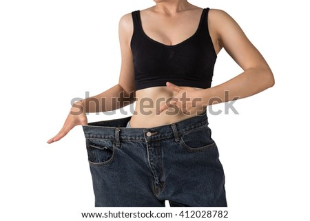 Slim Asian young female in big jeans showing her success weight loss - stock photo