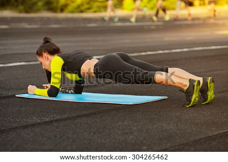 Slim athletic woman doing planking exercise in the stadium, sporty girl workout, outdoors  - stock photo