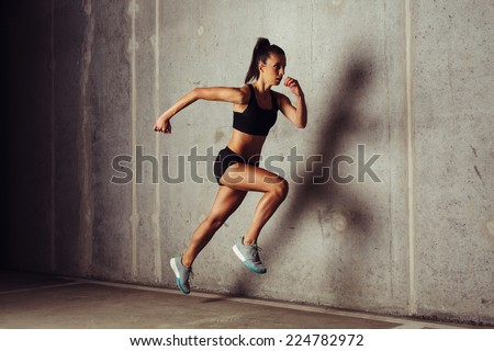 Slim attractive sportswoman running  against a concrete background - stock photo