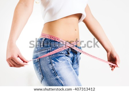 Slim Attractive Waist woman in jeans with tape measure show thin body.Diet and weight control.