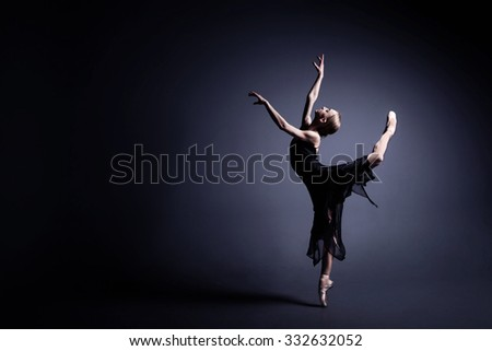 Slim ballerina is dancing in the dark - stock photo