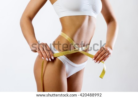 Slim beautiful woman with measure - stock photo