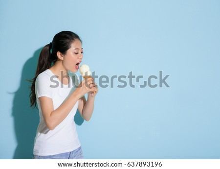 slim beauty female model standing on blue wall background eating delicious ice cream forget having sensitive tooth disease problem.