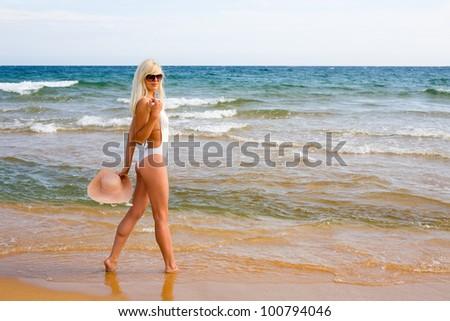 Slim blonde girl goes to the beach - stock photo