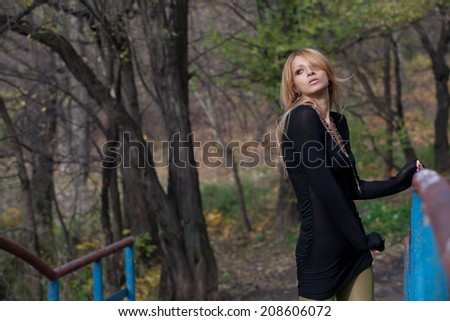 Slim blonde girl in short black dress posing on pedestrian bridge clear autumn day