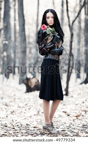 Slim brunette woman in a park. Ir-style colors. - stock photo