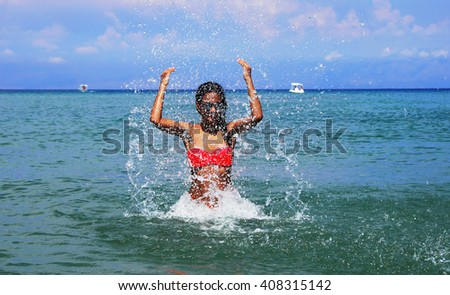 slim caucasian teenage girl with raised hands splashing water in the blue Ionic sea, Greece - stock photo