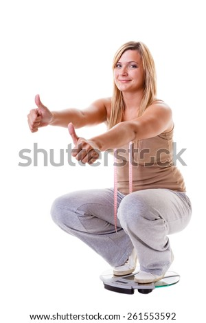 Slim down concept. Woman plus size large content girl on weight scale with measuring tape celebrating weightloss progress after healthy dieting, thumb up gesture - stock photo