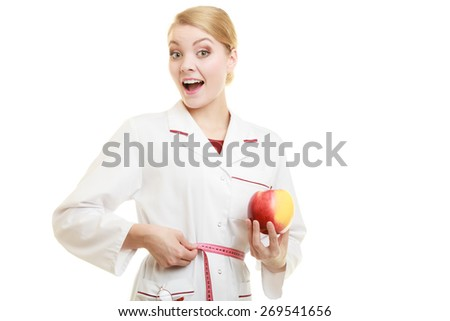 Slim down dieting concept. woman in white lab coat recommending healthy food. Doctor specialist dietitian holding fruit apple measuring her waist isolated. - stock photo