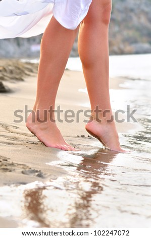 slim female legs steps to the sea - stock photo