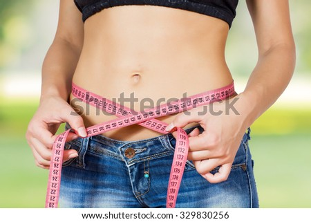 Slim Female with perfect healthy fitness body, measuring her thin waist with a tape measure. Caucasian young woman in jeans ,over nature background. Unrecognizable person.Diet and weight loss concept.