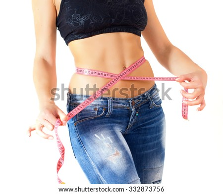 Slim Female with perfect healthy fitness body, measuring her thin waist with a tape measure. Caucasian young woman in jeans, over white background. Unrecognizable person.Diet and weight loss concept. - stock photo