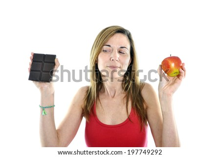 slim fit 40s Woman with Apple and Chocolate in Hands to choose health or temptation - stock photo