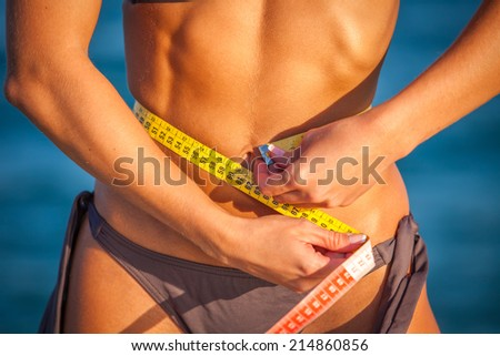 Slim fit woman at the beach in bikini with measure tape - stock photo