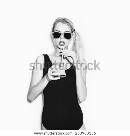 Slim funky blonde woman in black body drink cocktail with orange juice. Emotion. Toned. White background, not isolated - stock photo