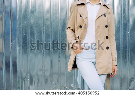 Slim girl in jeans, a beige coat and white shirt outdoors in spring, copy space. - stock photo
