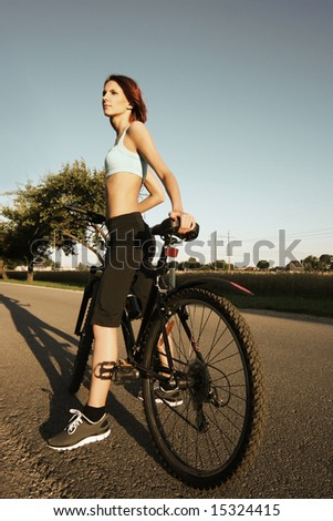 slim girl on bicycle outdoors - stock photo