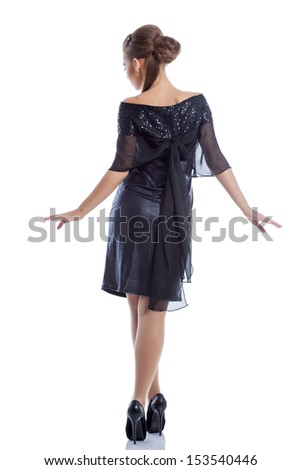 Slim girl posing in cocktail dress, back to camera - stock photo