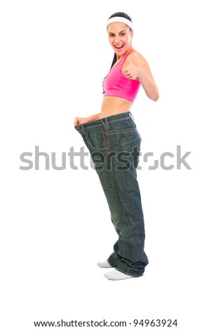 Slim girl pulling oversize jeans and showing thumbs up. Weight loss concept - stock photo